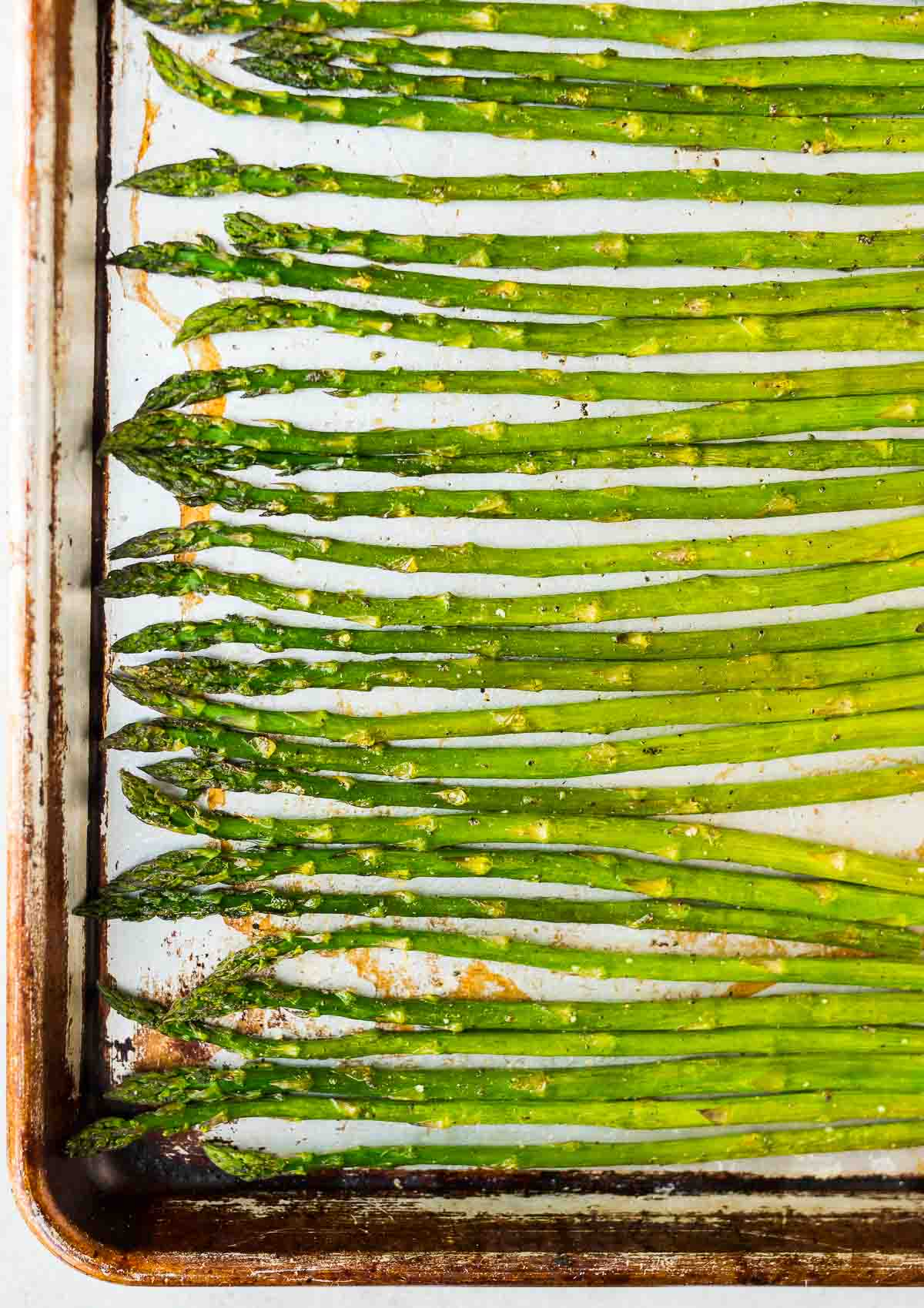 Roasted asparagus spears on a baking sheet