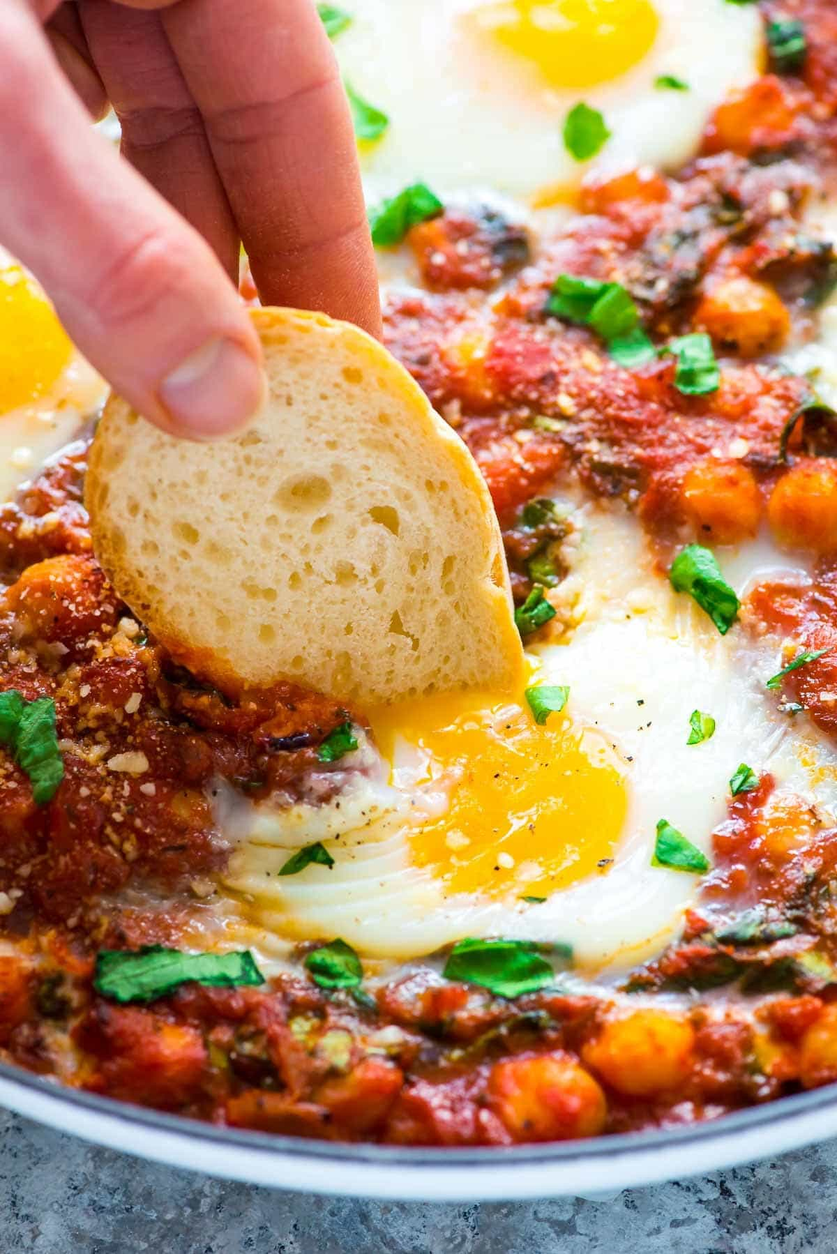 Italian Baked Eggs in Purgatory – Eggs simmered in a garlic tomato sauce with chickpeas, spinach, basil, and Parmesan. Easy, healthy, budget-friendly, and DELICIOUS! Recipe at wellplated.com | @wellplated