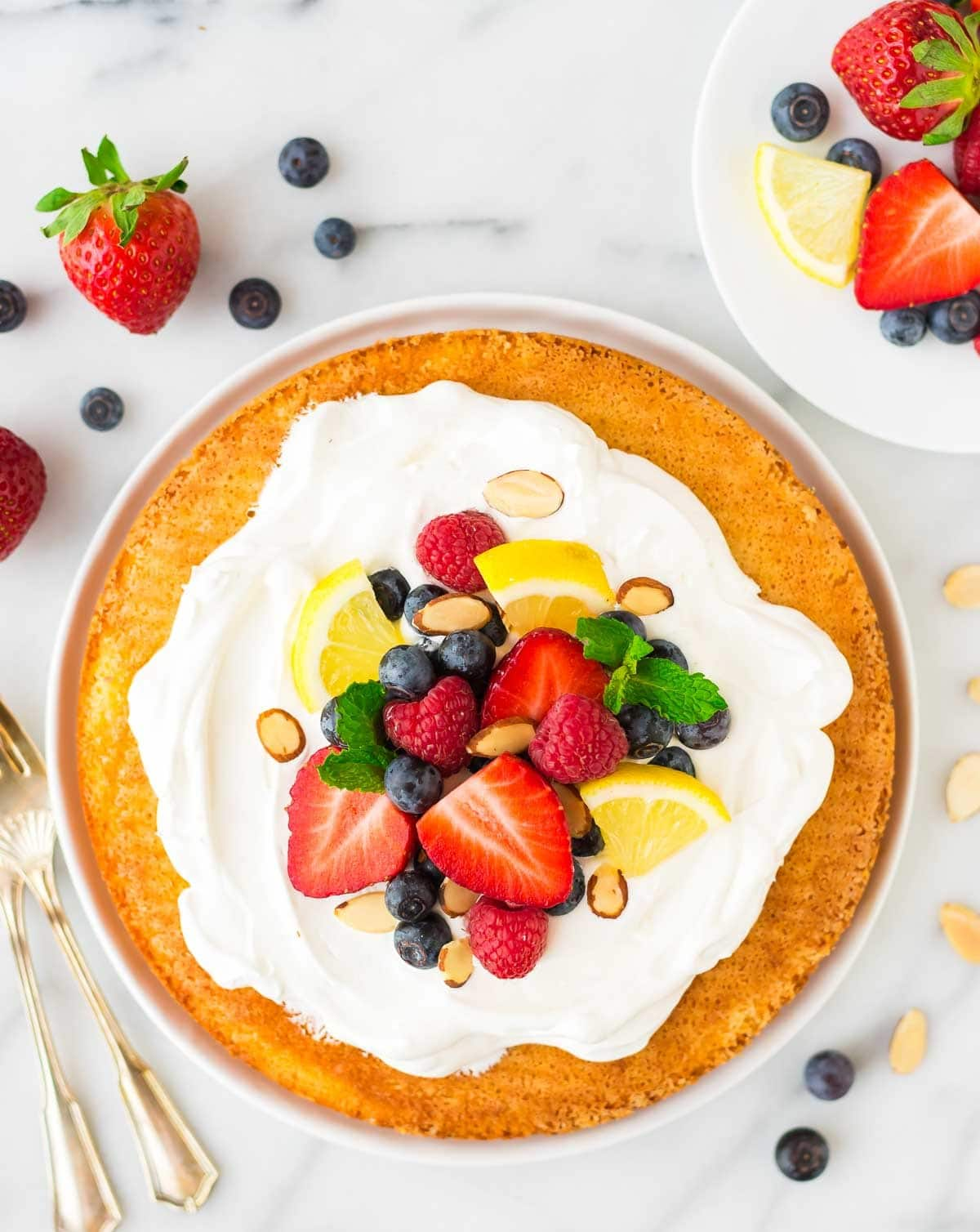 Flourless Almond Cake with Lemon and fresh berries – light, fluffy gluten free dessert made with almond flour, eggs, and sugar. Easy to make and perfect for holidays and parties. Recipe at wellplated.com | @wellplated