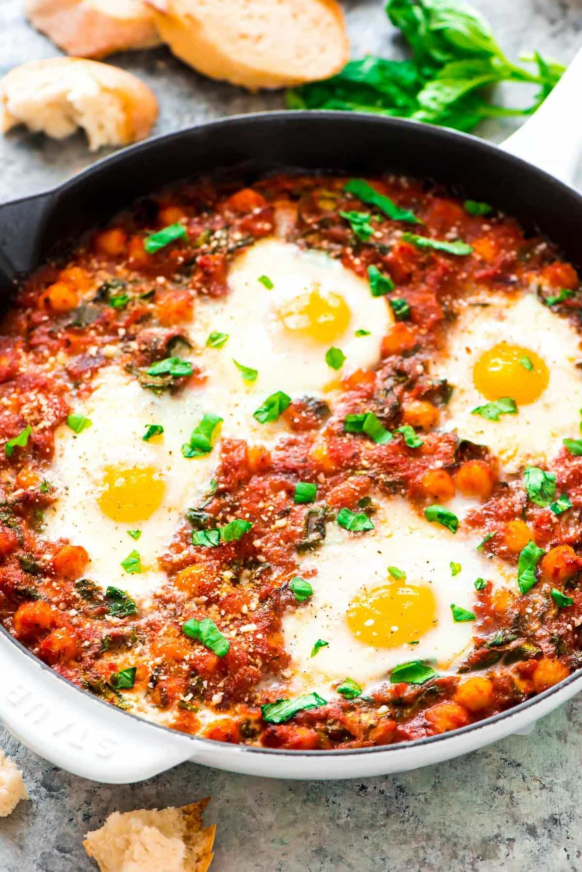 Eggs in Purgatory, Italian style – Easy, budget friendly, and filling! Eggs baked in a zesty tomato sauce with chickpeas, spinach, basil, and Parmesan. Recipe at wellplated.com | @wellplated