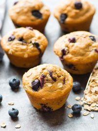 5 healthy blueberry muffins on a granite counter next to a scoop of rolled oats and fresh blueberries