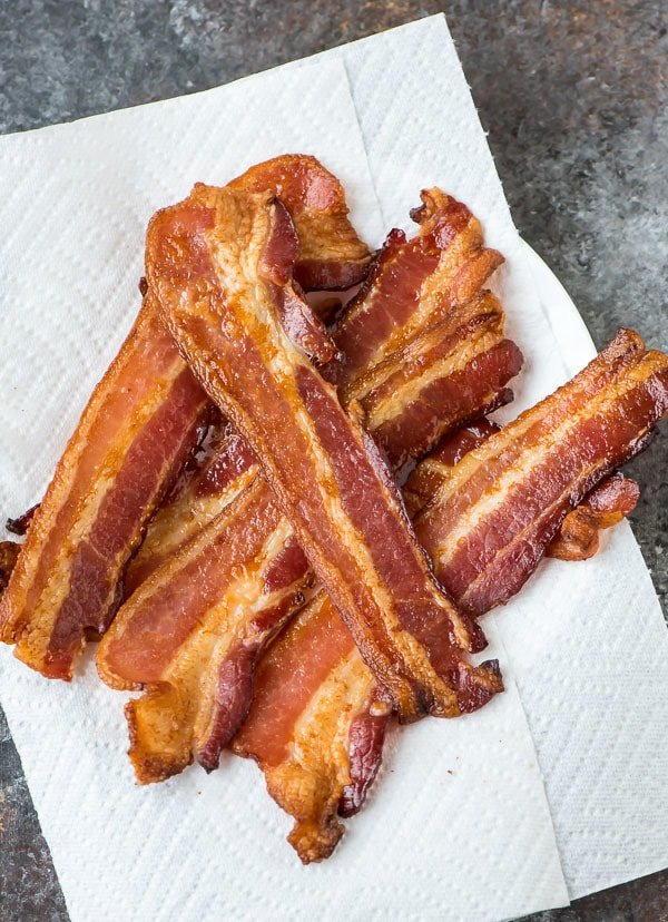 oven baked bacon has grease removed by draining on layers of white paper toweling
