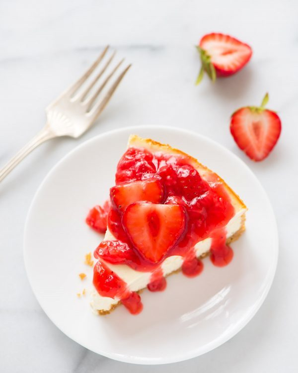 Skinny Greek Yogurt Cheesecake with fresh strawberry sauce. SO FLUFFY. No one will every know it's lightened up! Recipe at wellplated.com | @wellplated
