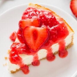 slice of Greek yogurt cheesecake topped with fresh strawberry sauce