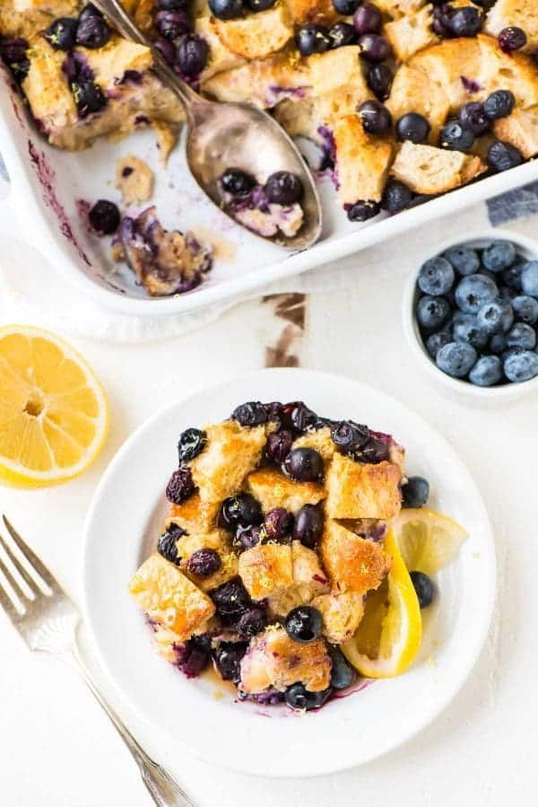 A white plate and baking dish full of blueberry lemon French toast