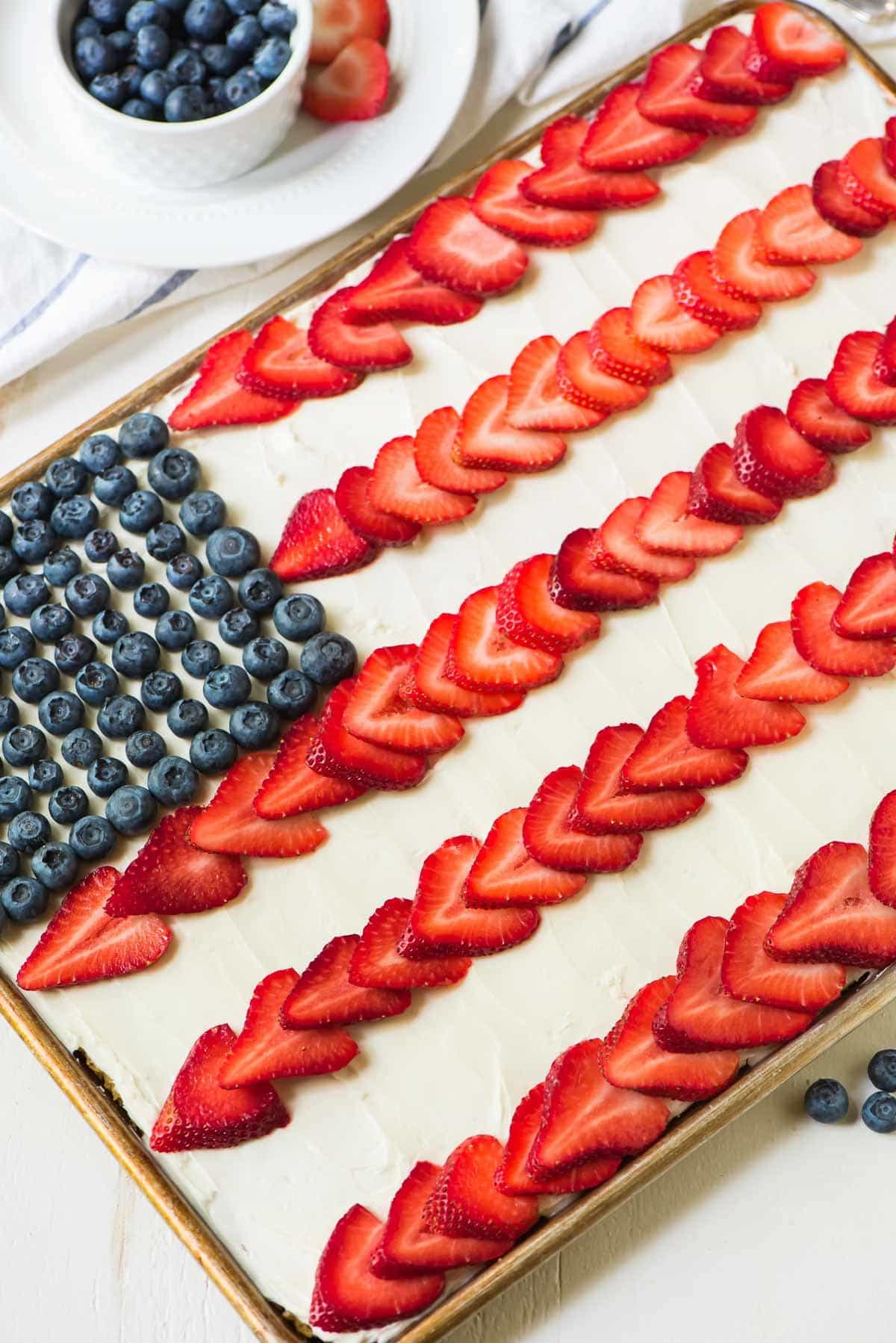 American Flag Cake. Perfect patriotic dessert for the Fourth of July, Memorial Day or Labor Day! A healthy version of the classic recipe featuring a soft and fluffy yellow sheet cake made with honey, Greek yogurt, and whole wheat flour, topped with Greek yogurt cream cheese frosting, fresh strawberry, and blueberry. Recipe at wellplated.com | @wellplated