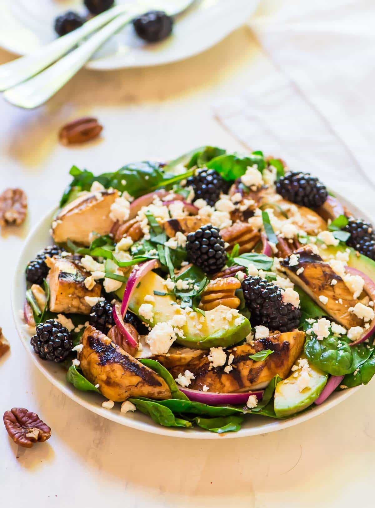 Summer grilled chicken salad in a bowl with blackberries, feta and pecans