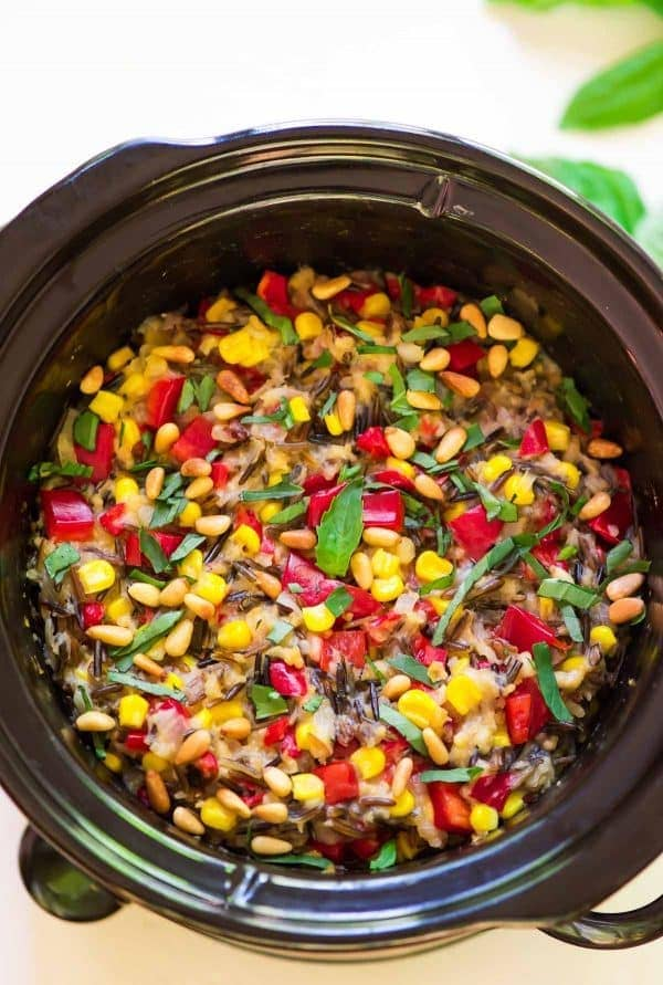 slow cooker wild rice pilaf with sweet corn, basil, and bell peppers sitting in a crock pot
