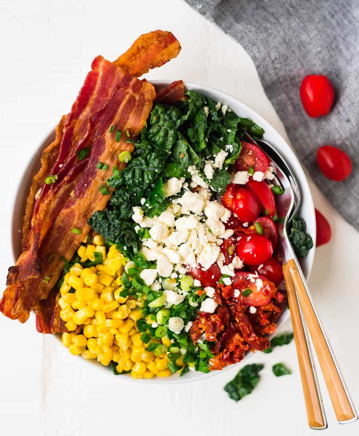 A bowl with bacon, kale, feta, corn, and tomatoes