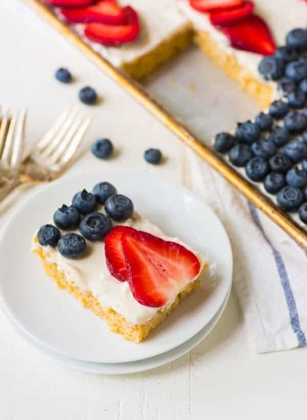 Easy Flag Cake recipe – looks absolutely beautiful and is easy to make! Fluffy yellow sheet cake topped with cream cheese frosting and decorated with fresh blueberry and strawberry to look like an American Flag. The perfect Fourth of July dessert. Recipe at wellplated.com | @wellplated
