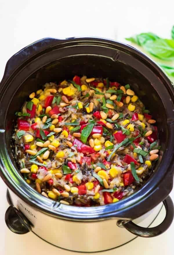 crock pot full of wild rice pilaf with peppers, corn and basil