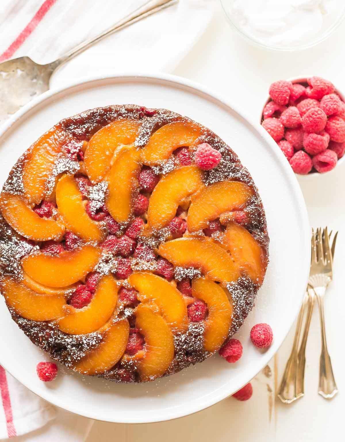 Unbelievable Peach Upside Down Cake with fresh raspberries.