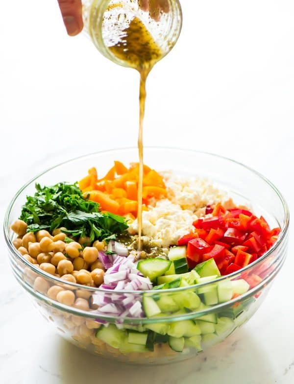Chopped chickpea salad in a glass bowl with dressing being poured over the top