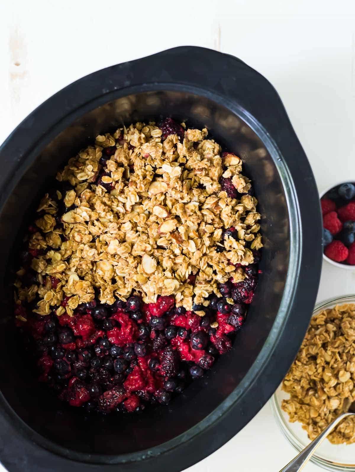 slow cooker full of ingredients to make triple berry crisp