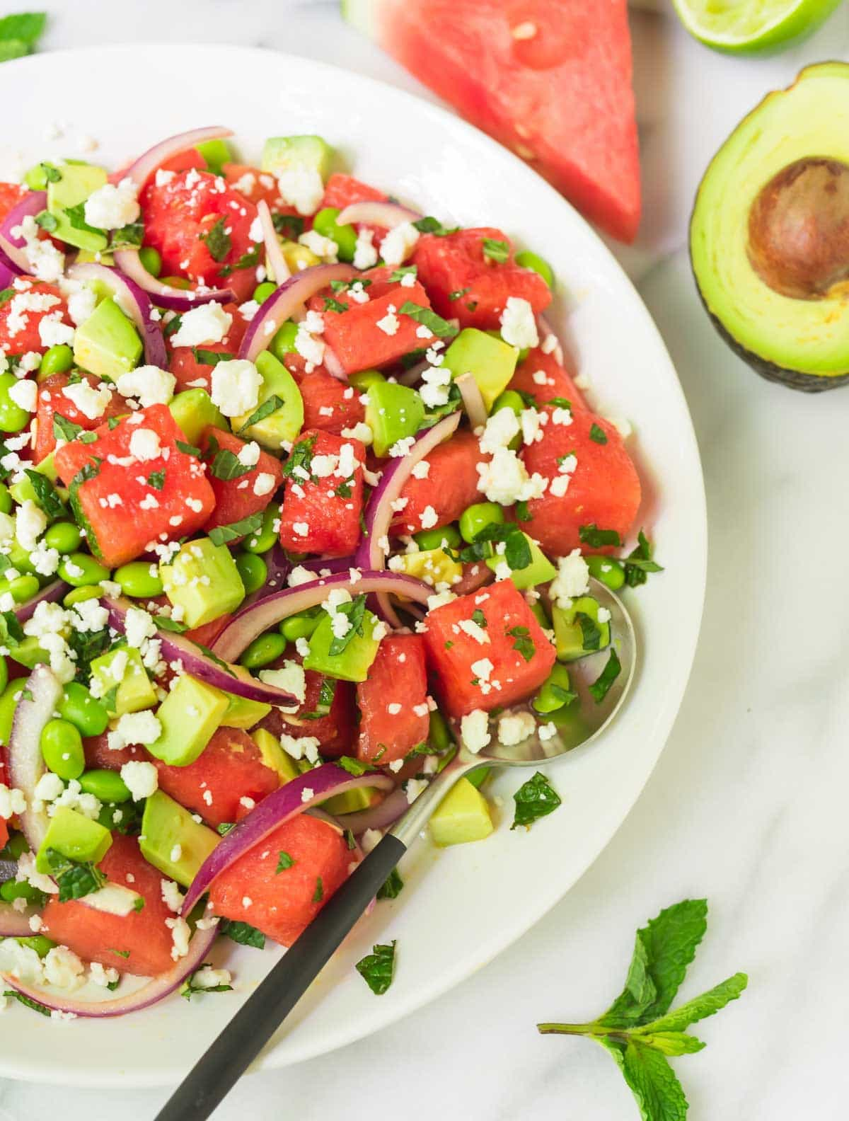 A watermelon salad with feta in a white serving bowl