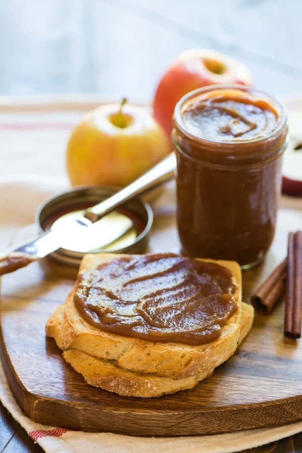homemade apple butter spread on toast sits in front of a mason jar full of the apple butter