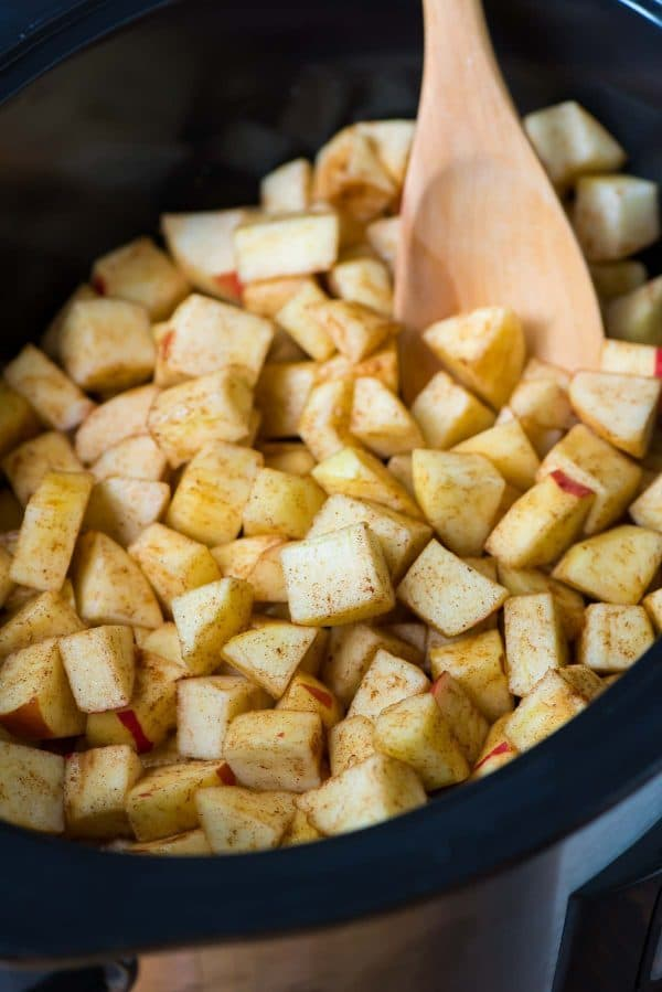 fresh diced apples dusted with cinnamon being stirred in a slow cooker