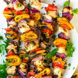 Five grilled orange kabobs on a white plate