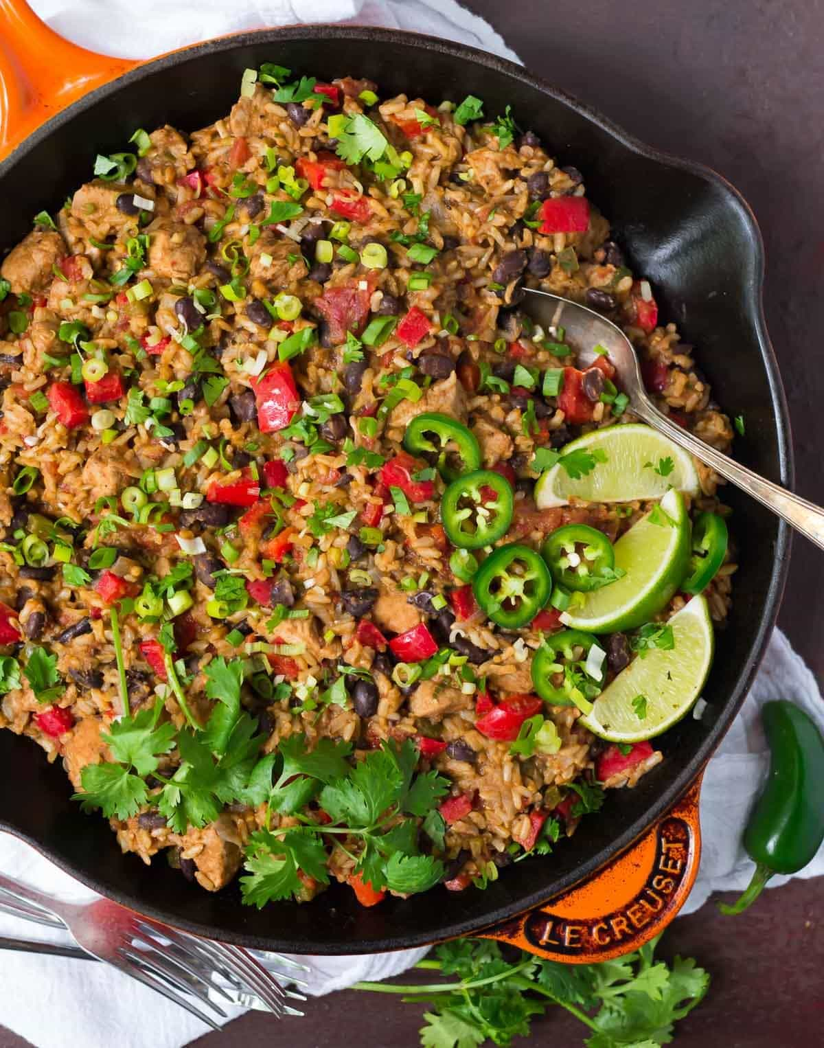 Healthy Mexican Chicken and Rice Skillet on a white napkin with jalapenos and cilantro