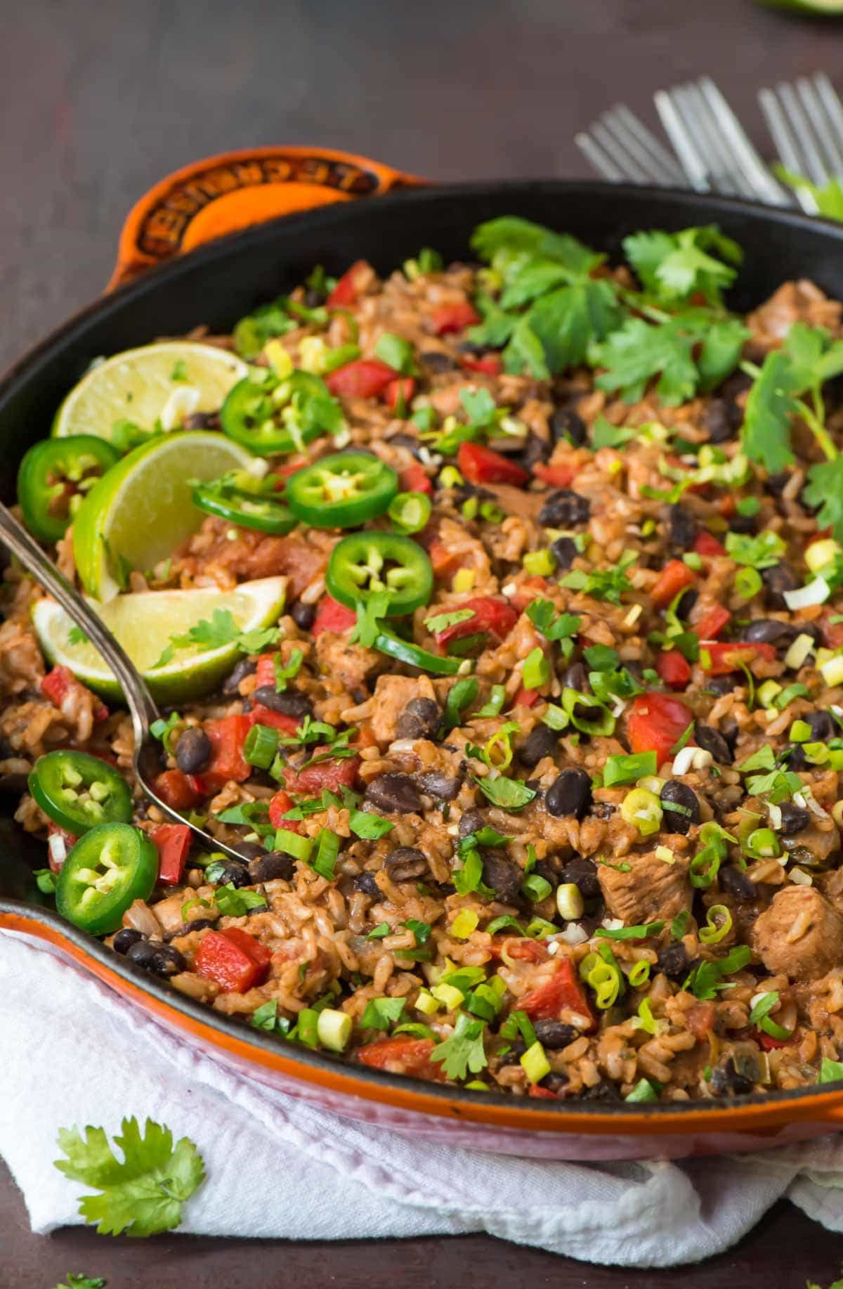 Mexican Chicken and Rice with black Beans in a cast iron skillet garnished with green onions and limes