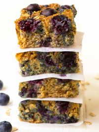 A stack of quinoa breakfast bars with blueberries