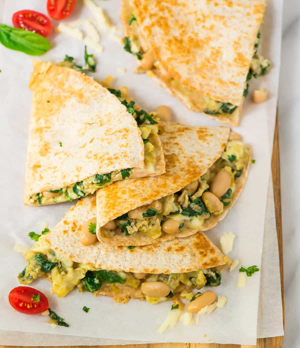 A vegetarian breakfast quesadillas cut into wedges on parchment paper and garnished with parsley and tomatoes