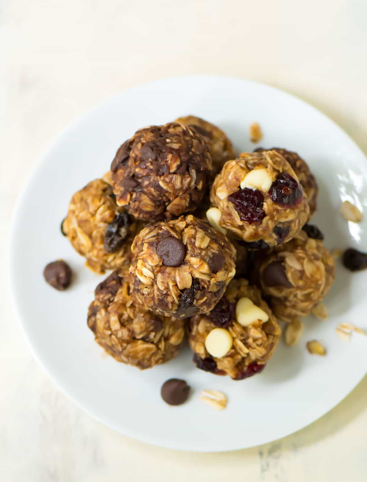 small white plate with a stack of no bake energy balls with chocolate chips and dried fruits