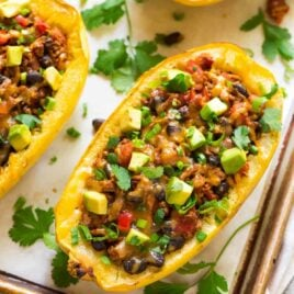 Healthy Taco Spaghetti Squash Boats with Cheese, Ground Turkey, and Black Beans. Easy, filling, and low carb! Great for busy families. Everyone loves this recipe! {gluten free}. Recipe at wellplated.com