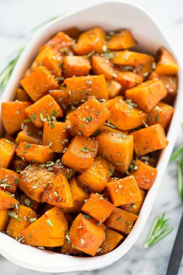 Maple roasted butternut squash cubes with cinnamon and served in a bowl topped with fresh rosemary