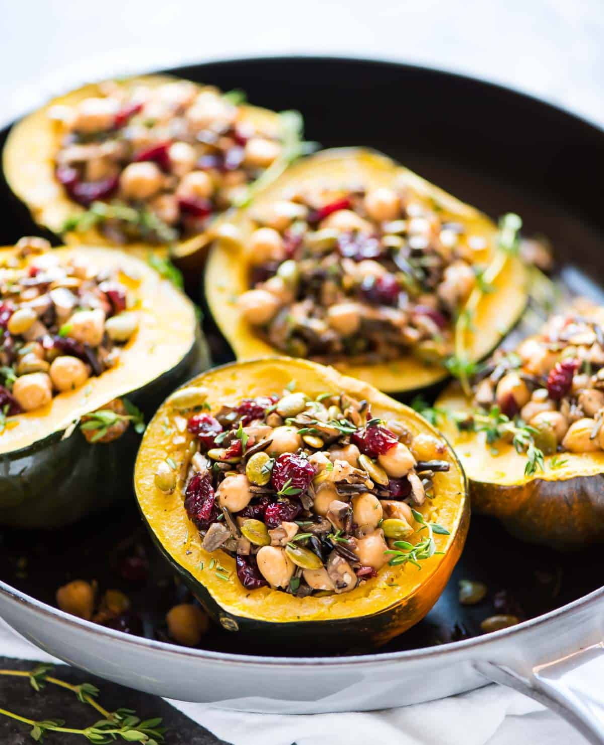 Five acorn squash stuffed with wild rice, cranberry, mushroom, and chickpeas in pressure cooker