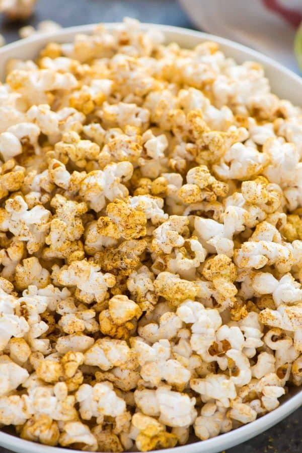 Taco seasoning makes for a delicious and easy flavored popcorn that's perfect for a healthy party appetizer, snack to keep at your desk, and movie nights. Simple recipe with chili powder, lime, and nutritional yeast.