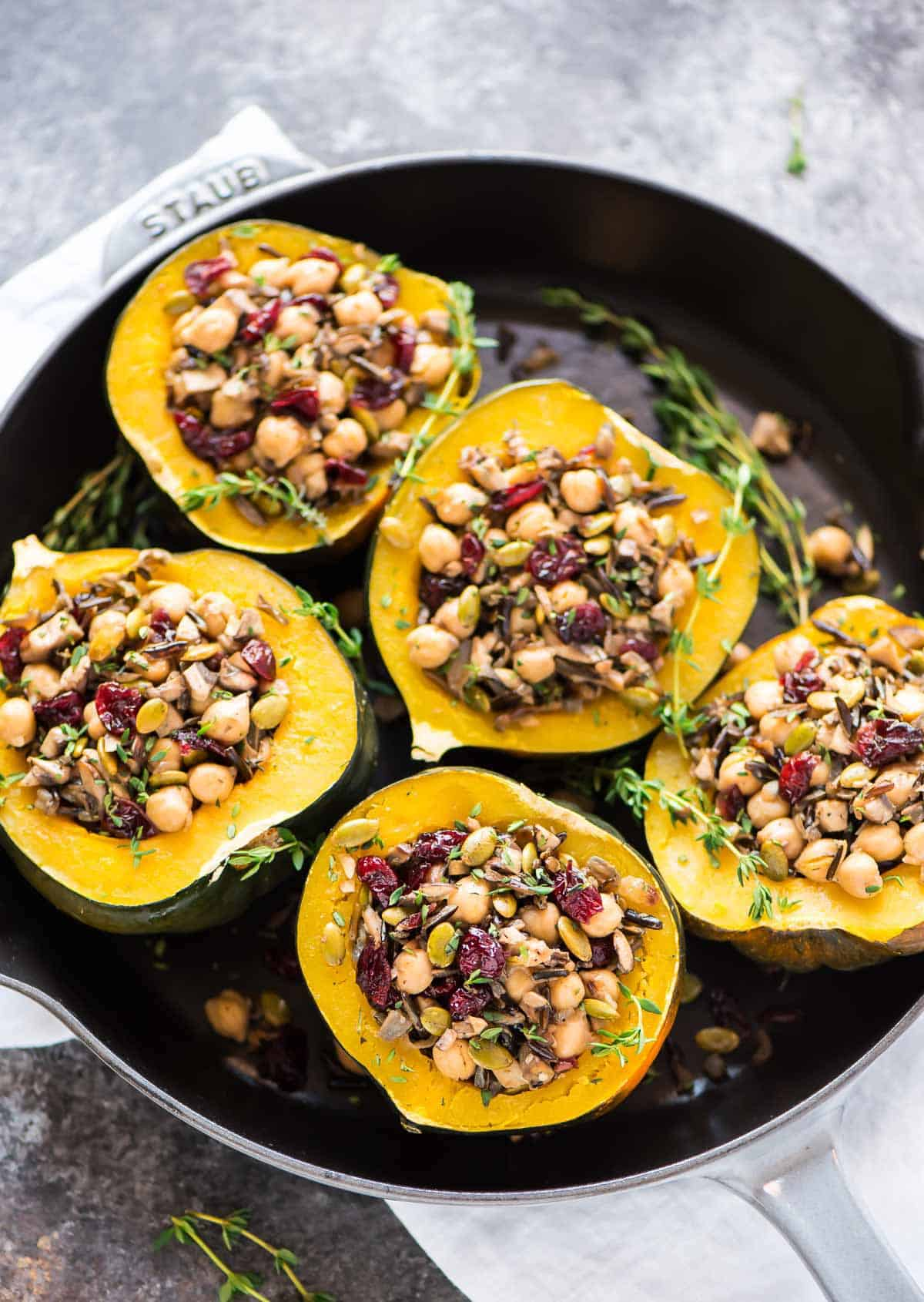 Delicious Stuffed Instant Pot Acorn Squash with Wild Rice, Cranberry, Mushroom, and Chickpeas arranges in a cast iron skillet