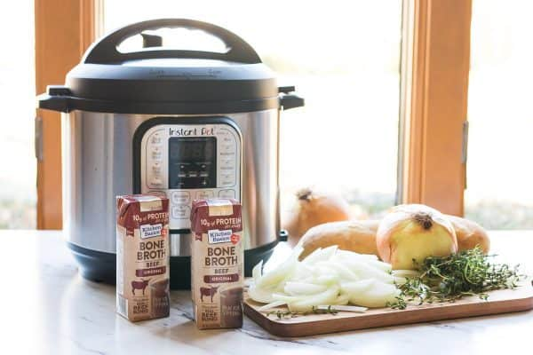 Instant Pot pressure cooker next to a cutting board with the ingredients to make French Onion Soup