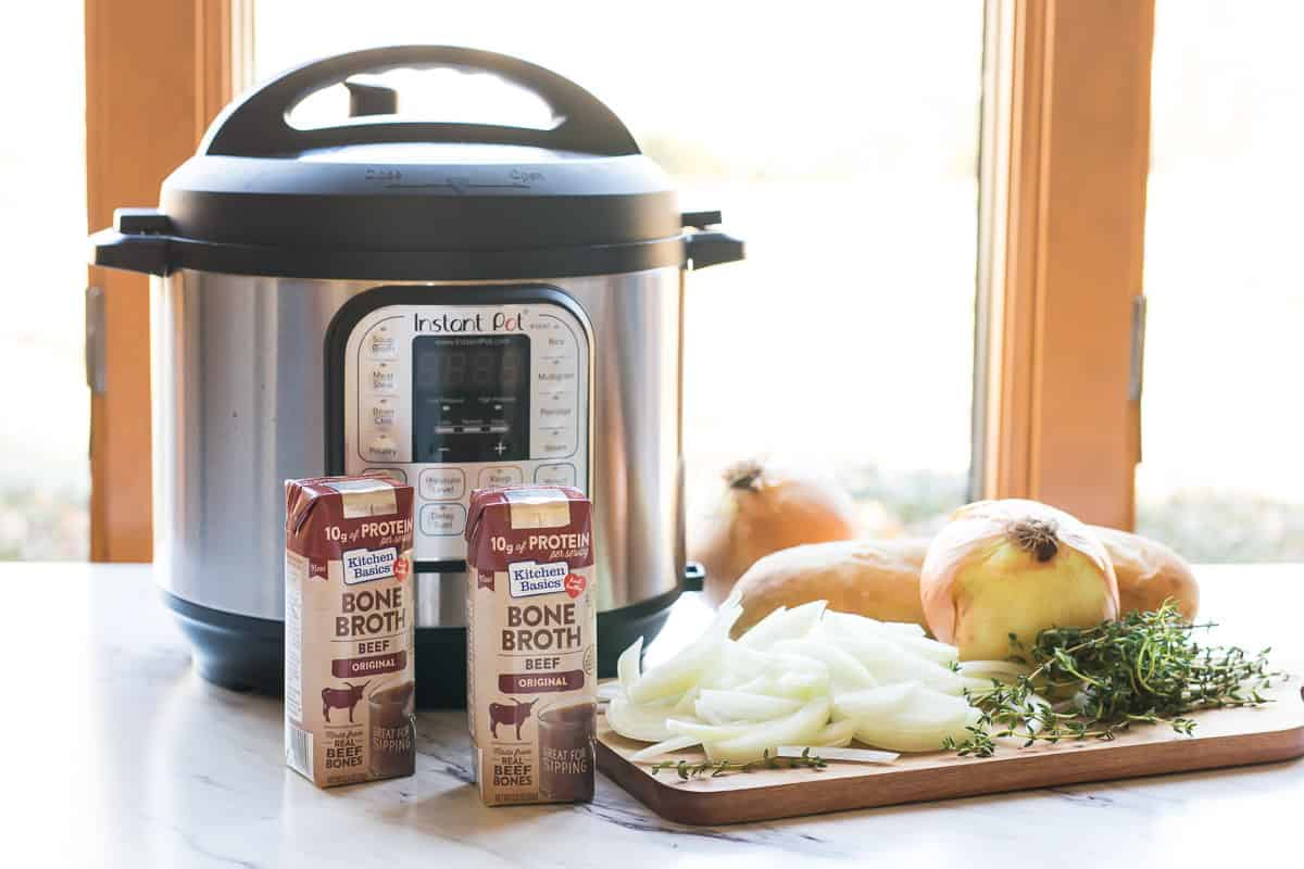 Instant Pot pressure cooker next to a cutting board with the ingredients to make homemade French Onion Soup