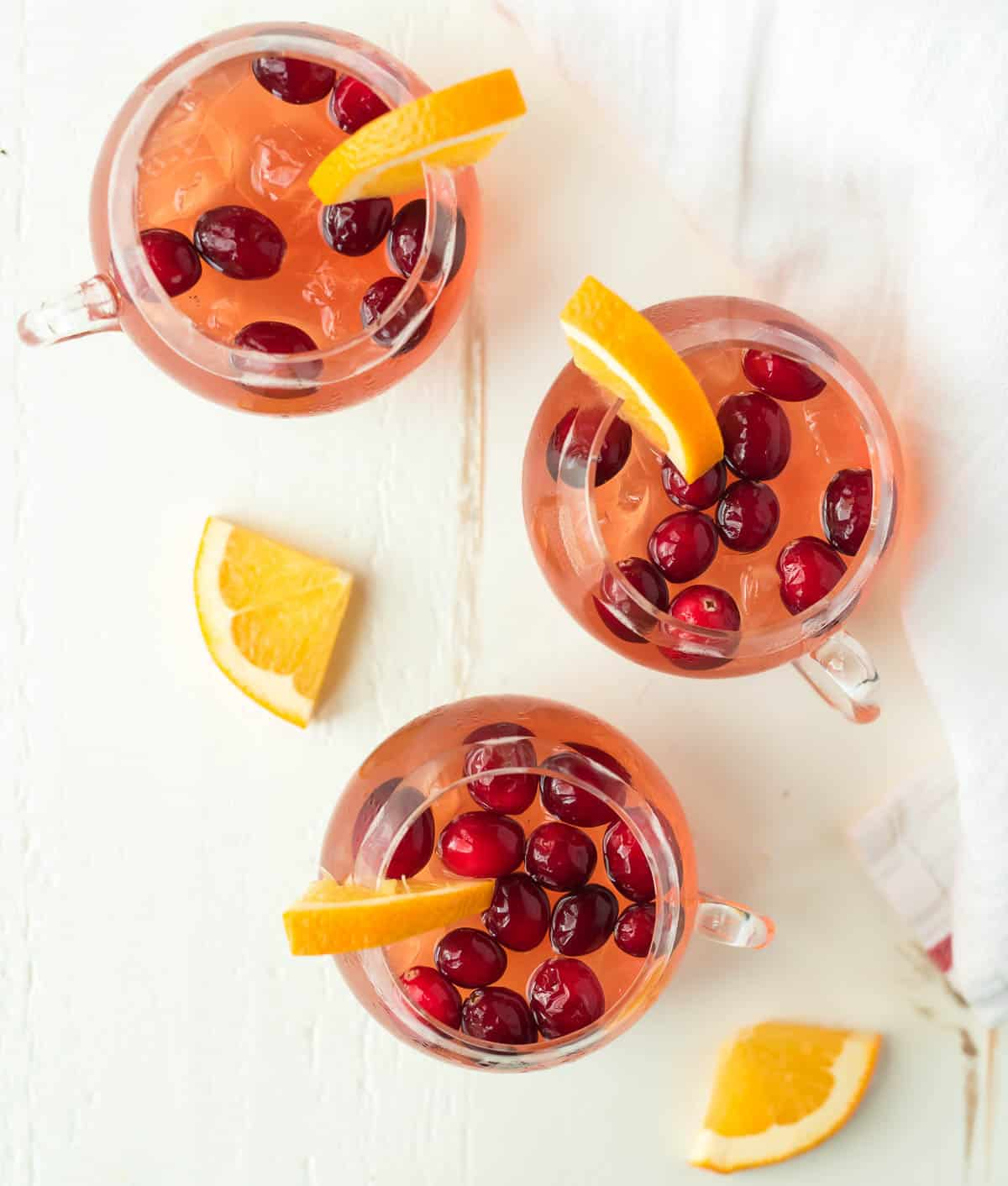 three glass punch glasses with pink punch topped with cranberries