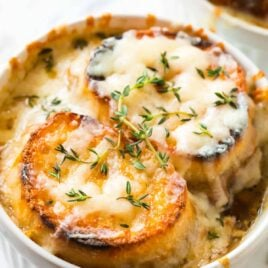 soup crock of Instant Pot French Onion Soup garnished with cheesy baguette croutons
