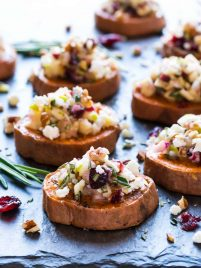 Baked Sweet Potato Rounds with Goat Cheese, Cranberry, Apple, and Pecans. An easy and addictive sweet potato appetizer! Healthy baked sweet potato slices roasted until crispy, then topped with a delicious combination of holiday flavors. Perfect easy appetizer for Thanksgiving, Christmas, and any party!