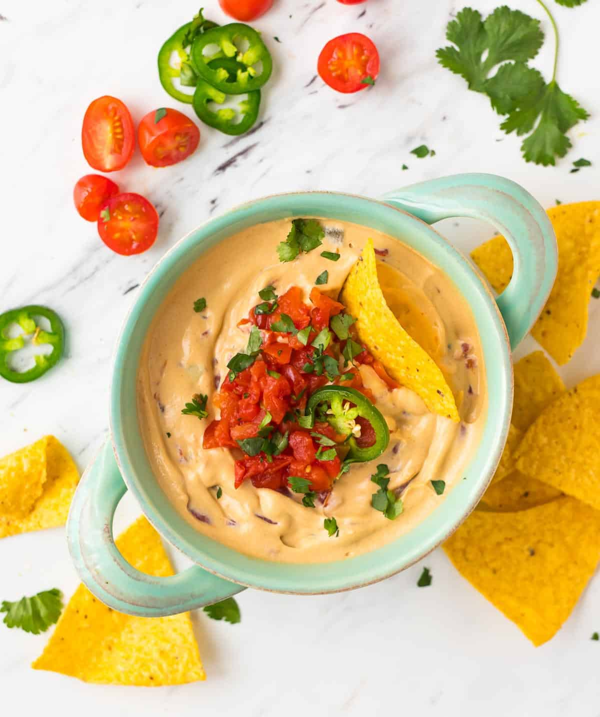 Vegan Queso Dip topped with cilantro and diced in a blue bowl with yellow corn tortilla chips