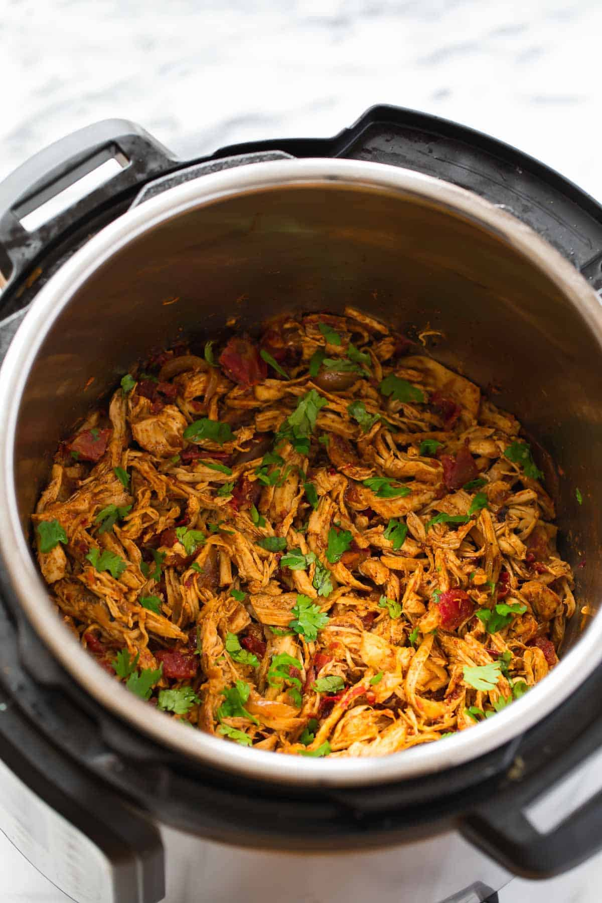 Shredded chicken cooked and seasoned in an Instant Pot for tacos.