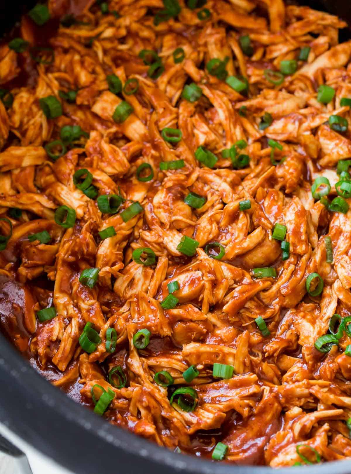 Shredded chicken in a slow cooker with bbq sauce and green onions