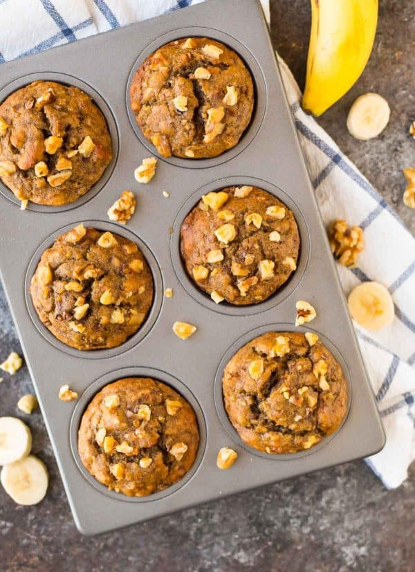muffin pan filled with healthy banana walnut muffins sits on a white kitchen towel with blue stripes.