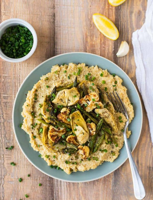 Creamy vegan risotto made with quinoa and almondmilk! Topped with delicious roasted cauliflower, asparagus, artichokes, and nutritional yeast.