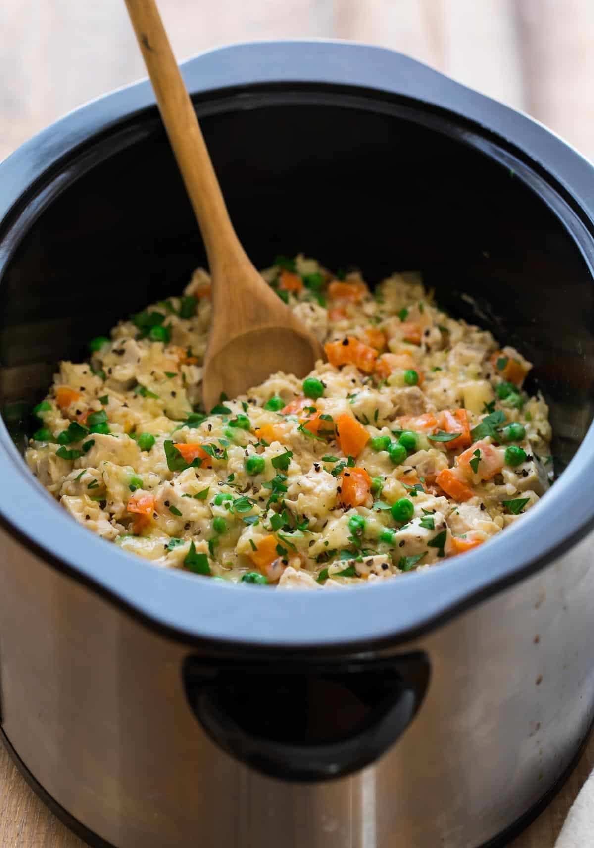 crock pot chicken and rice with vegetables being stirred with a wooden spoon