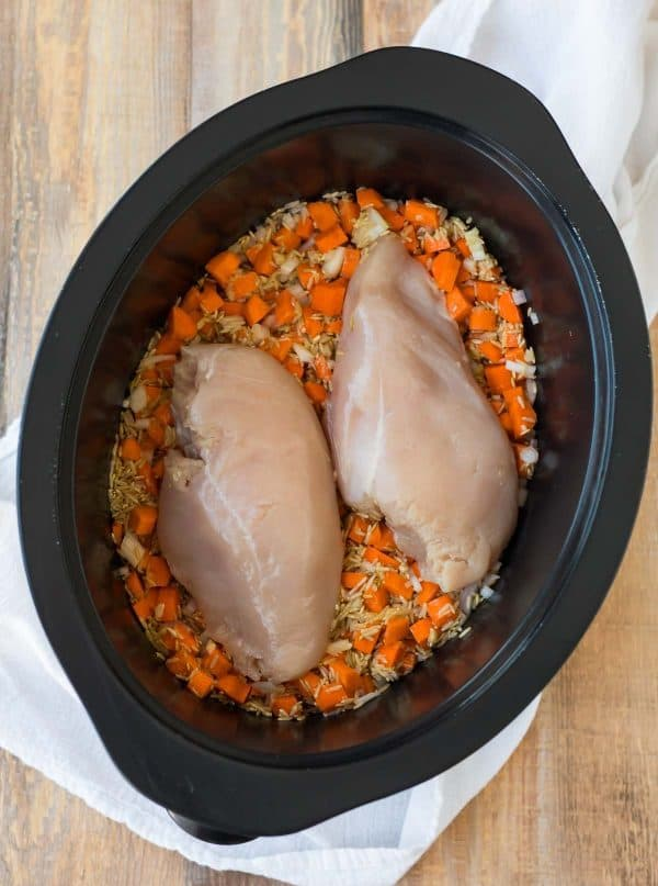 uncooked chicken breasts and other ingredients in a slow cooker to make a chicken and rice dinner