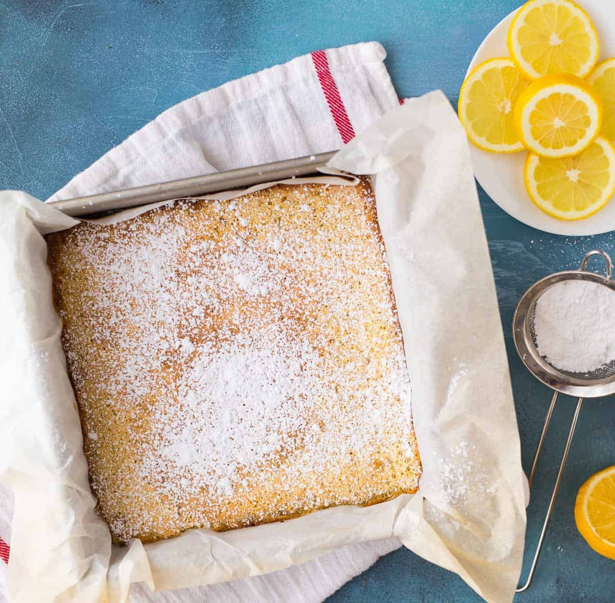 The best lemon bars baked in a square pan dusted with powdered sugar on a blue background