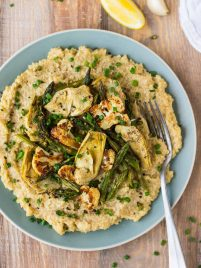 Vegan risotto on a blue plate with artichokes