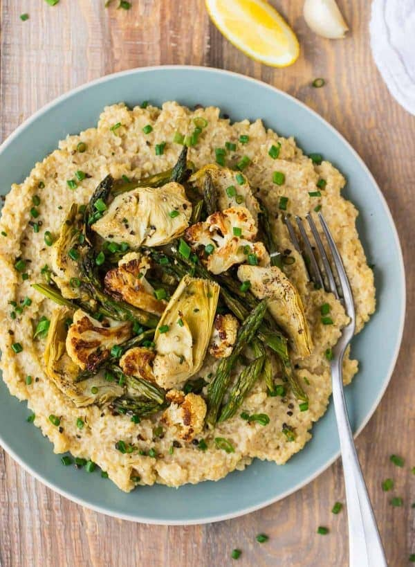 An easy vegan risotto recipe made with quinoa, cauliflower, and nutritional yeast, topped with asparagus and veggies.