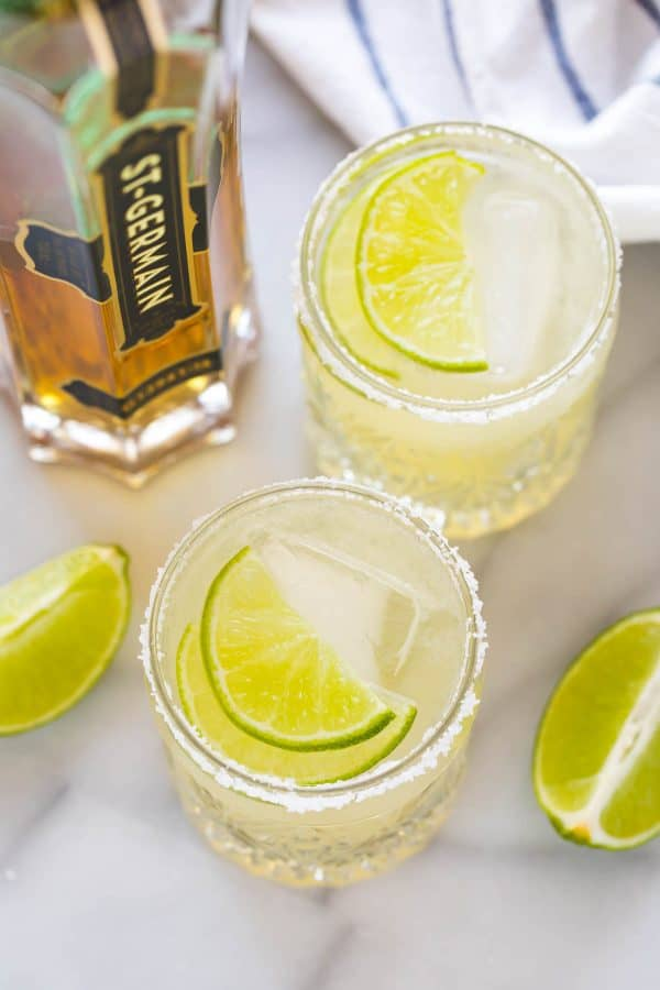 Two St. Germain margaritas with lime slices on a counter