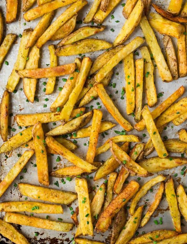 Crispy baked French fries on a baking sheet with seasoning