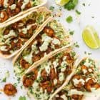 The BEST Healthy Shrimp Tacos with Cilantro Lime Sauce and Cabbage Slaw. Juicy, spicy, and so quick and easy! Cook on the stove or grill!